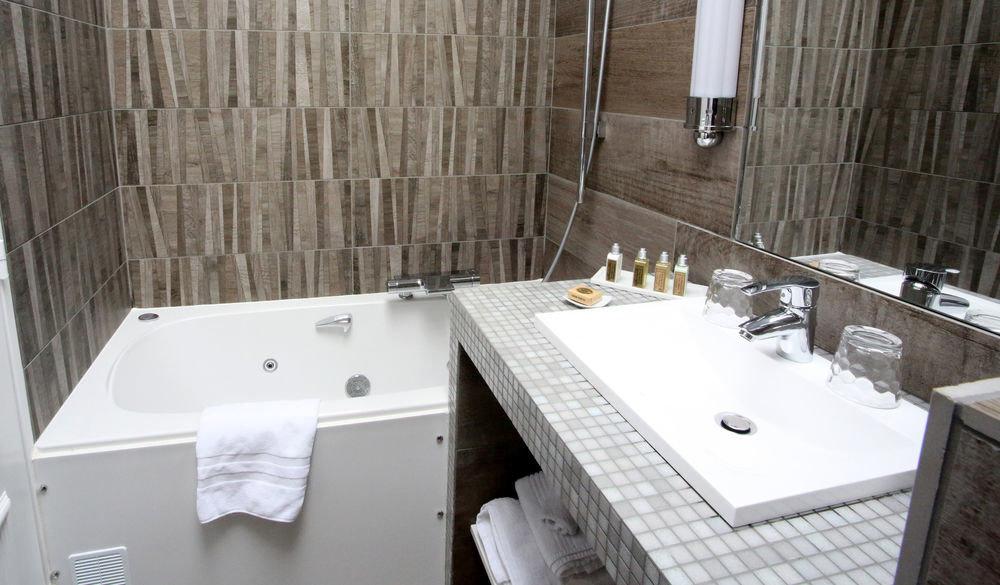 bathroom property vessel swimming pool bathtub house sink plumbing fixture jacuzzi home cottage flooring bidet tile tub tiled Bath