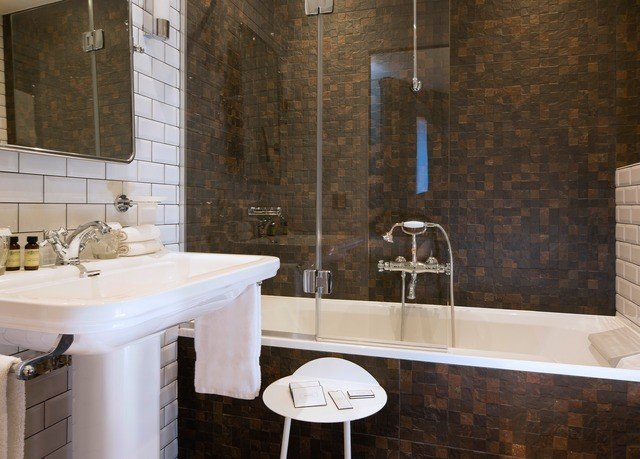 bathroom property sink countertop plumbing fixture home tile flooring toilet tiled tub bathtub Bath