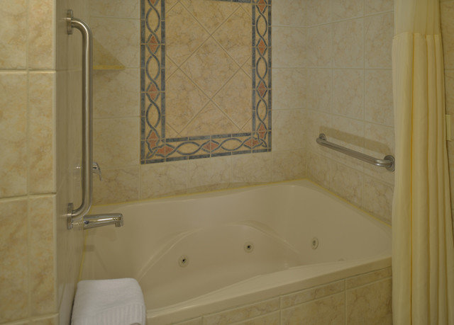 bathroom property white tub plumbing fixture flooring shower tile bathtub sink vessel Bath tiled tan