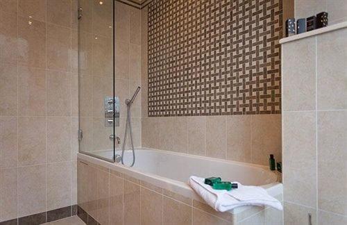 bathroom property scene tile plumbing fixture tiled sink flooring tub bathtub Bath tan