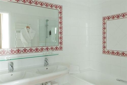bathroom sink mirror property white bathtub plumbing fixture toilet flooring tile tiled Bath tub
