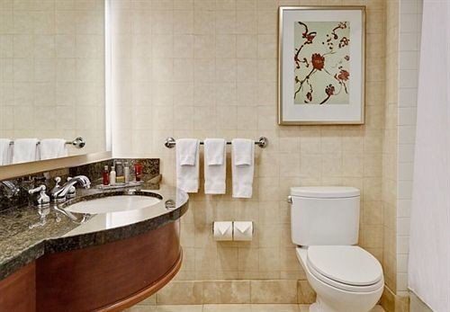 bathroom sink property toilet plumbing fixture flooring tile tiled tub Bath tan bathtub
