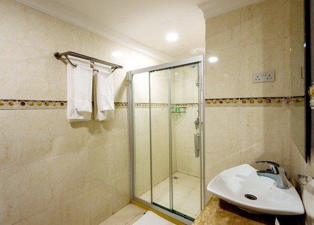 bathroom property sink plumbing fixture toilet public toilet flooring bathtub tiled tan Bath