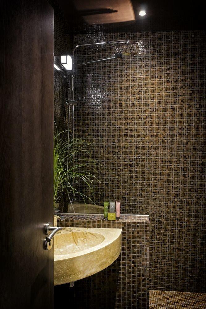 bathroom plumbing fixture tiled toilet tub lighting tile stall Bath bathtub stone tan