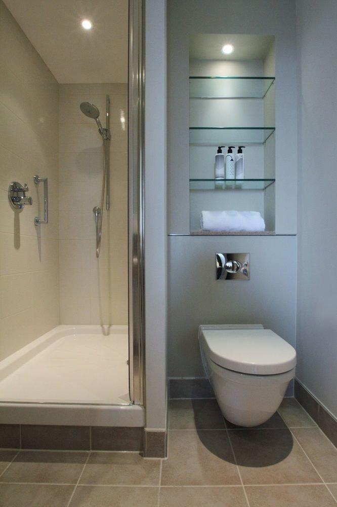 bathroom toilet property sink shower plumbing fixture white tile bidet flooring rack tiled tan tub Bath