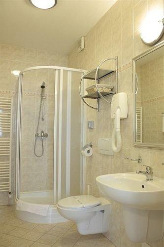 bathroom sink scene toilet plumbing fixture white bidet tile Bath tiled tan