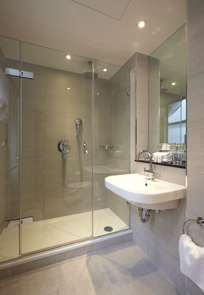 bathroom sink property mirror plumbing fixture toilet flooring tiled tile tan Bath