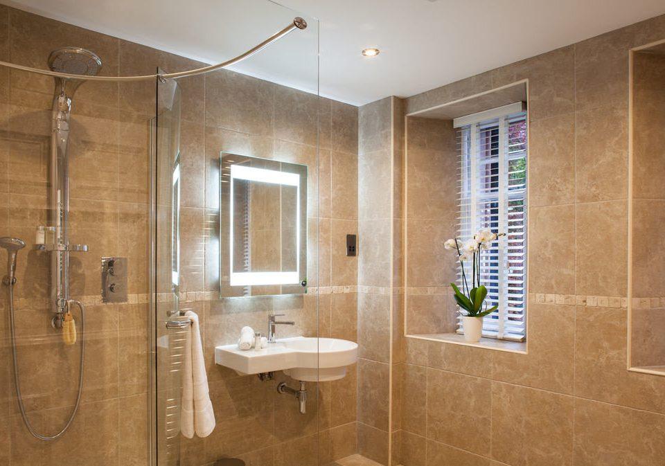 bathroom scene property sink plumbing fixture flooring tile tiled Bath tub tan