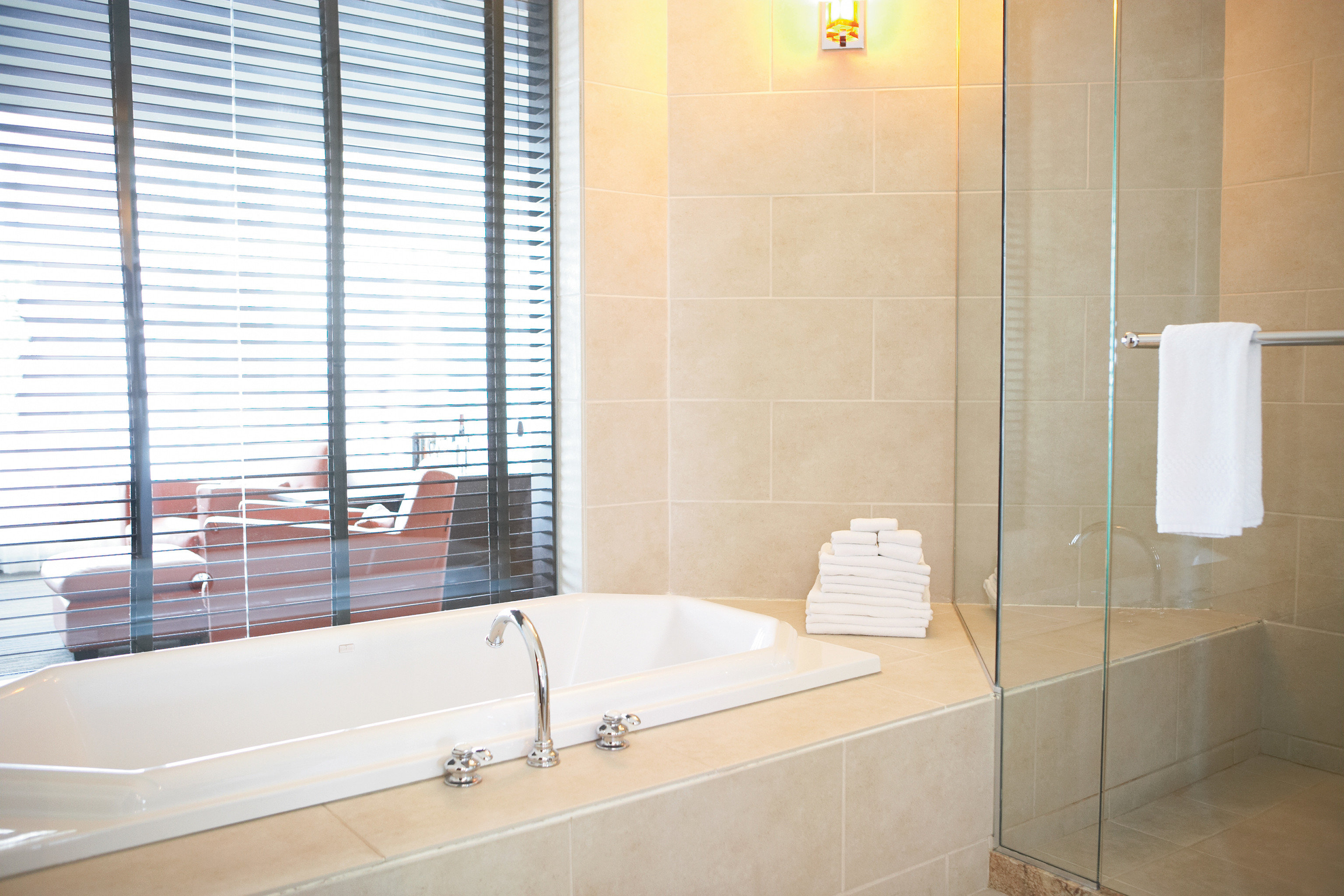 Bath Boutique Modern bathroom sink bathtub plumbing fixture toilet vessel tile flooring tiled tub tan