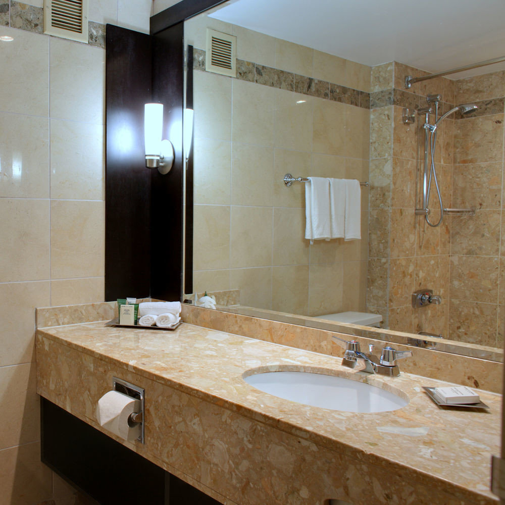 bathroom sink mirror large property counter countertop double plumbing fixture cabinetry vanity big cottage material Kitchen toilet tile tan bathtub tub Bath