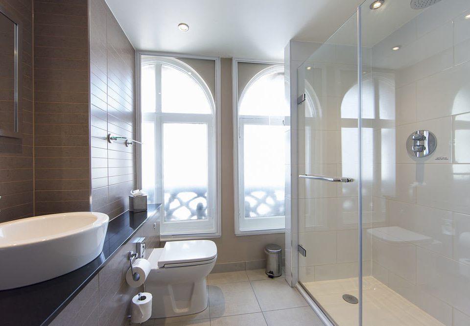bathroom property toilet plumbing fixture sink daylighting bathtub flooring tub tile tiled Modern Bath