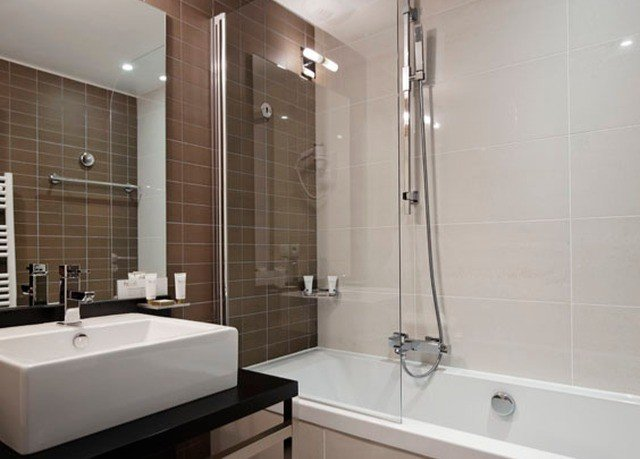 bathroom property shower plumbing fixture sink tub bathtub toilet flooring tiled tile Modern Bath