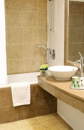 bathroom sink tile flooring plumbing fixture hardwood counter bathtub bidet laminate flooring Bath tiled tub Modern tan
