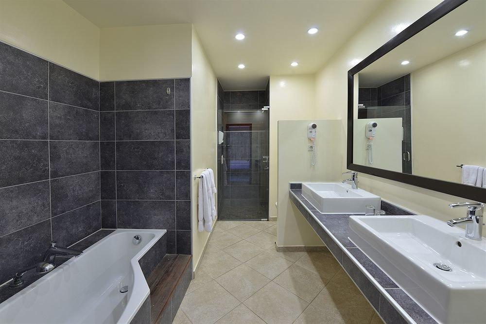 bathroom sink mirror property toilet tub Suite plumbing fixture flooring public toilet bathtub Bath tile Modern tiled clean