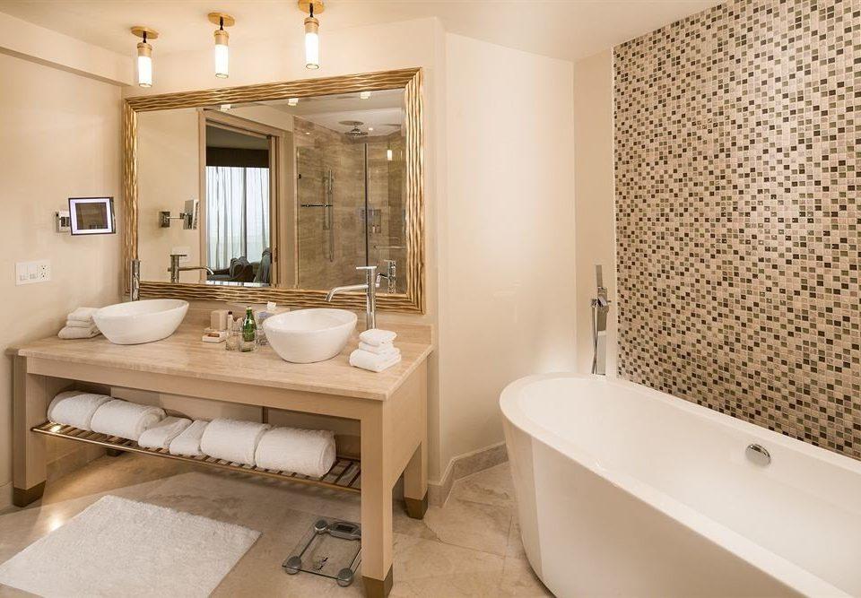 bathroom mirror property sink Suite home shower tub bathtub flooring Bath Modern tile tiled tan