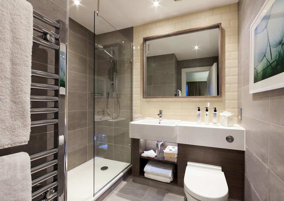 bathroom mirror property toilet sink home condominium Suite tub tile Modern tiled bathtub Bath