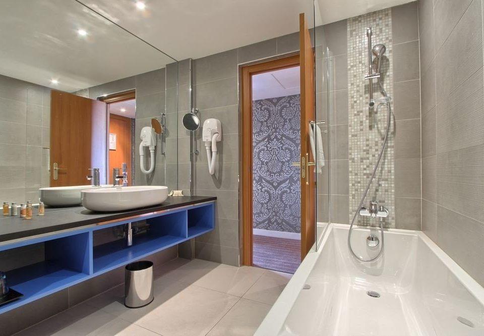 bathroom sink property toilet plumbing fixture flooring Suite bathtub tub Modern tile Bath