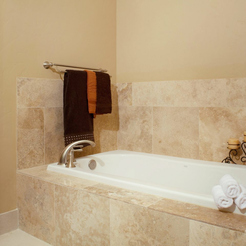 Bath Rustic bathroom property bathtub plumbing fixture sink tub flooring white bidet tile vessel tan tiled