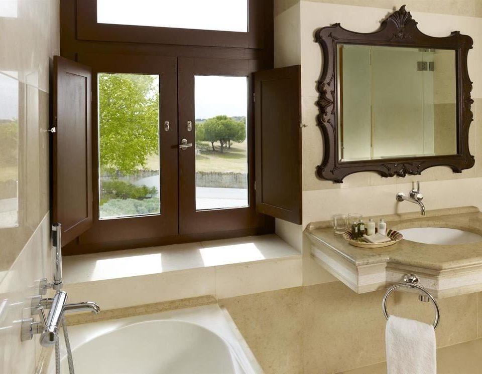 bathroom property sink home Suite plumbing fixture cottage bathroom cabinet bathtub tub Bath tiled tan