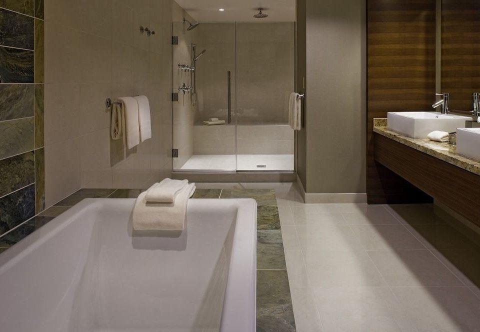 bathroom mirror sink property plumbing fixture toilet flooring counter tub bathtub Suite tile Bath