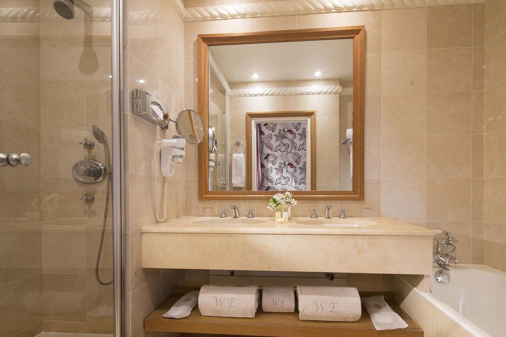 bathroom mirror property sink plumbing fixture toilet home bathtub Suite flooring cabinetry tub tan Bath