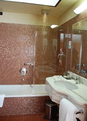 bathroom sink property mirror toilet Suite flooring swimming pool bathtub plumbing fixture tile tiled tub Bath