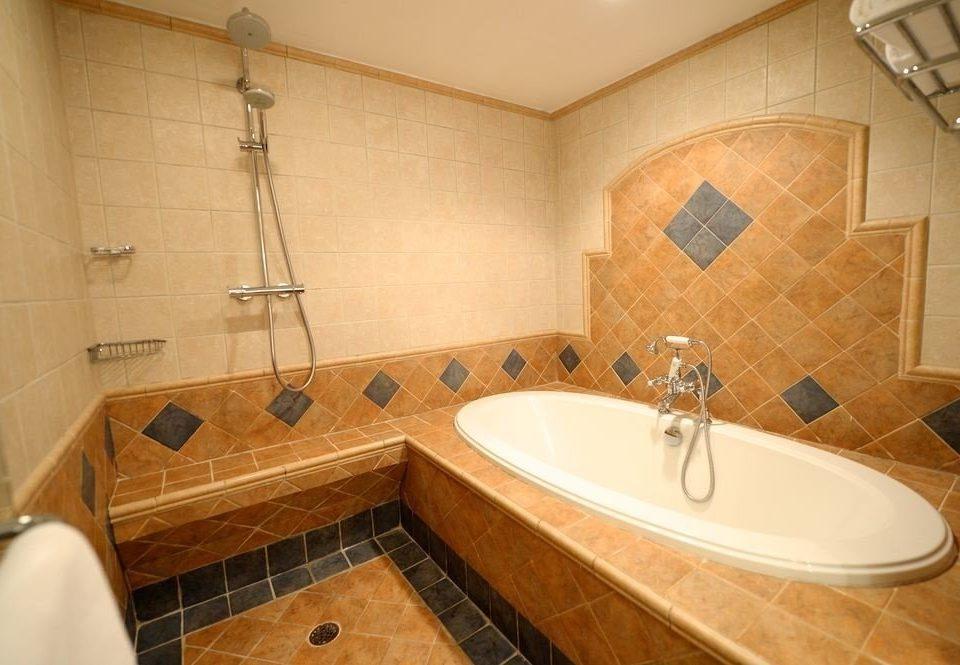 bathroom property sink vessel toilet tile tub Suite flooring cottage bathtub Bath tiled water basin tan