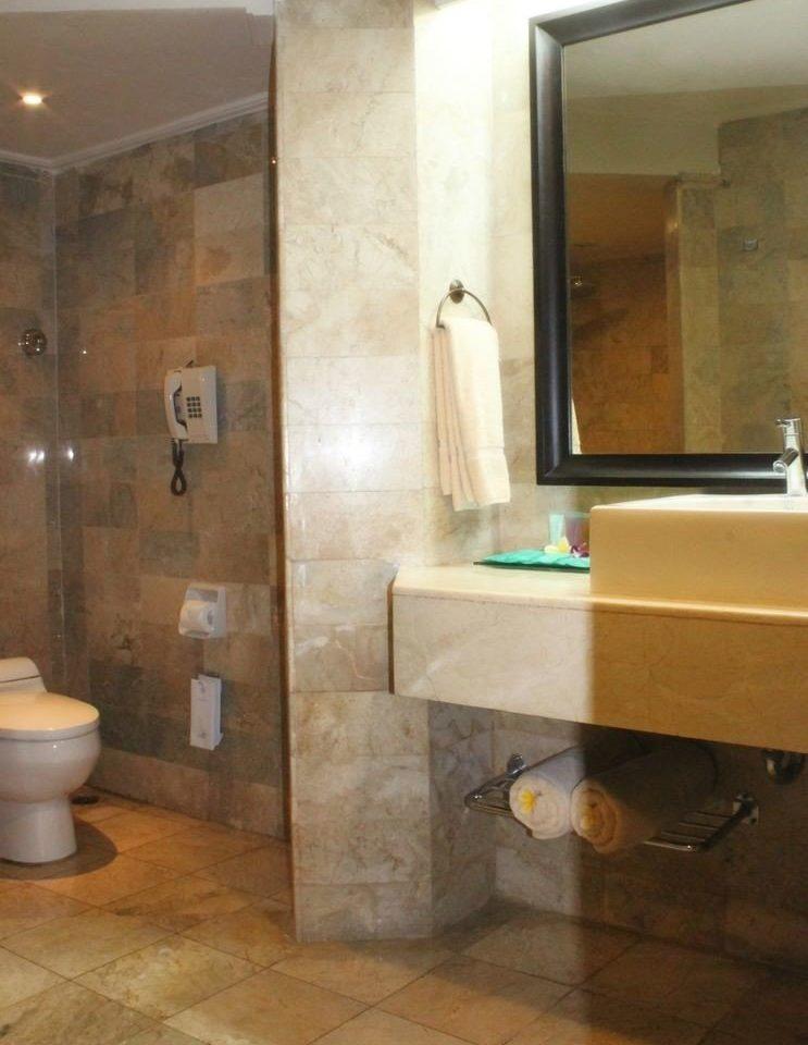 bathroom property sink plumbing fixture flooring tile Suite bathtub Bath tub tan