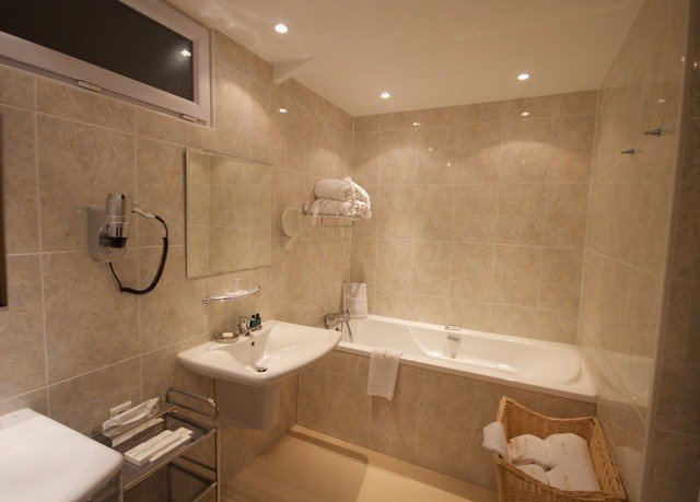 bathroom property sink plumbing fixture Suite toilet tub bathtub tile Bath tiled