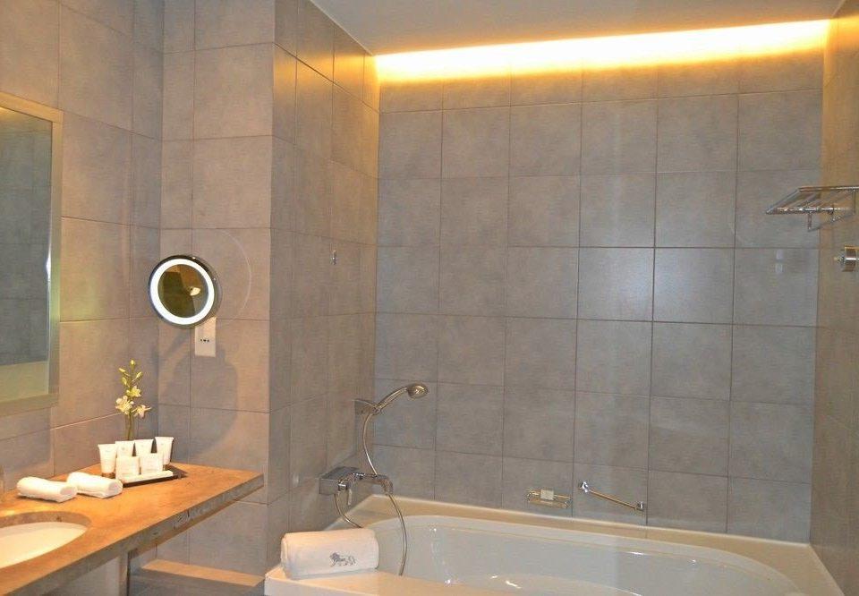 bathroom property sink toilet plumbing fixture bathtub Suite light tub tiled tile Bath