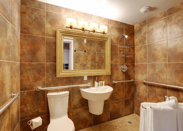 bathroom toilet property sink plumbing fixture Bath towel Suite flooring cabinetry tub tile bathtub tan