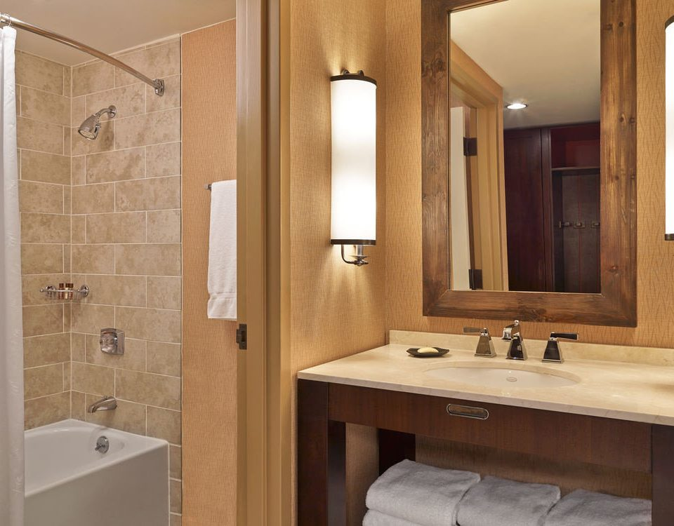 bathroom sink mirror property plumbing fixture towel cabinetry home Suite Bath tub tile tan bathtub