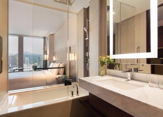 bathroom mirror sink property condominium Suite home toilet long tub bathtub tile tan Bath