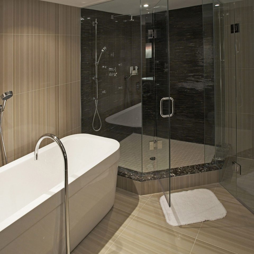 bathroom property scene bathtub plumbing fixture Suite flooring public toilet toilet tub tile tiled Bath