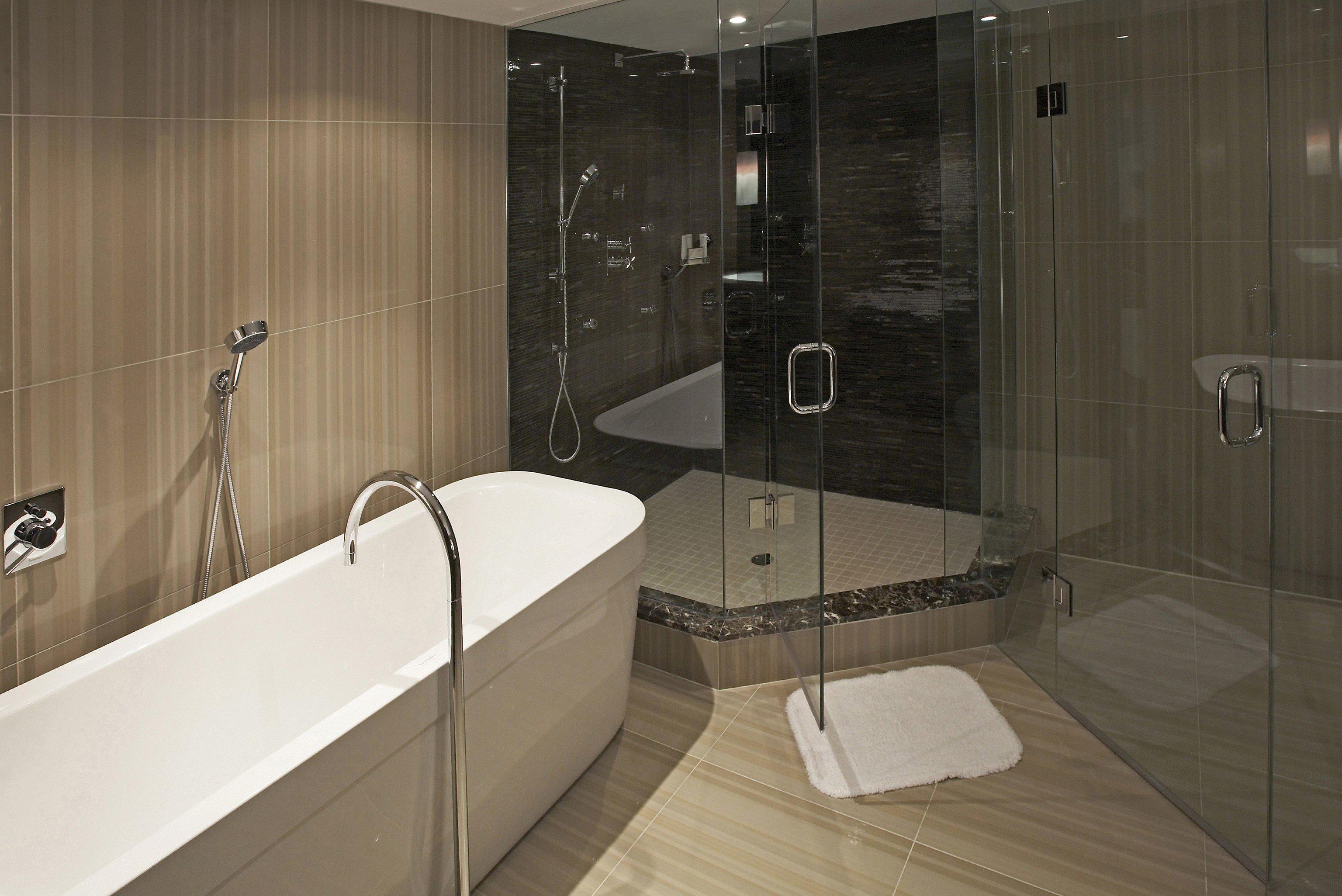 bathroom property scene bathtub plumbing fixture Suite flooring public toilet toilet tub tile tiled Bath