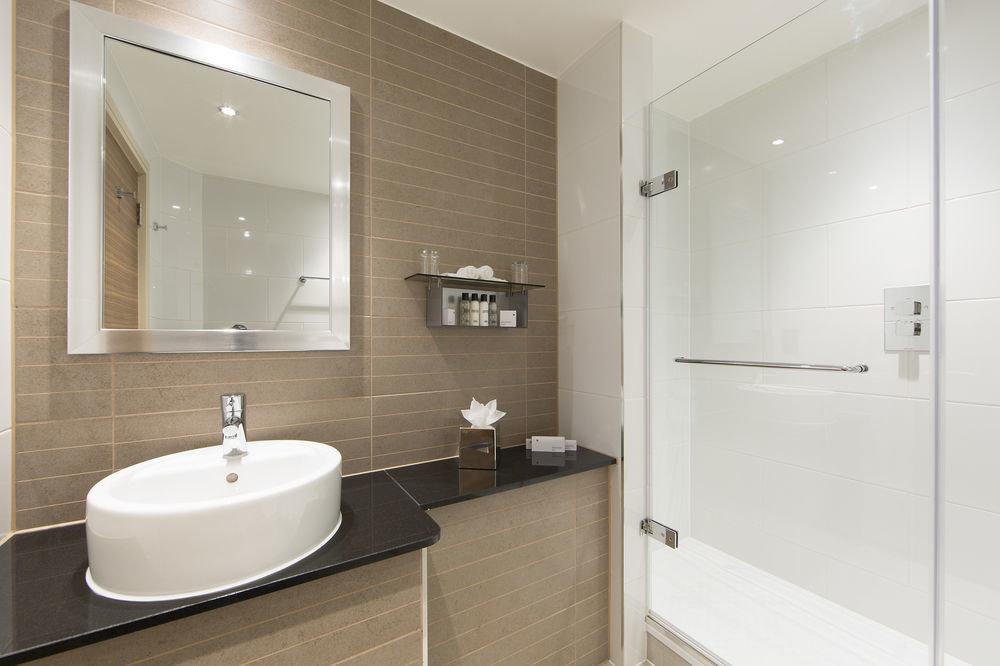 bathroom mirror sink property plumbing fixture bathtub bidet flooring bathroom cabinet toilet rack