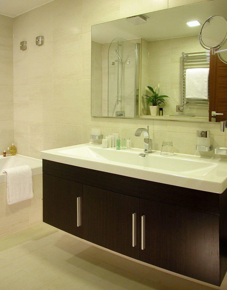 bathroom mirror sink bathtub countertop plumbing fixture cabinetry bathroom cabinet flooring clean tile tan