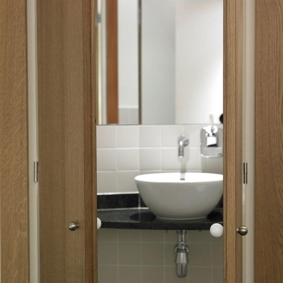 bathroom mirror toilet sink plumbing fixture door flooring bidet bathroom cabinet tiled