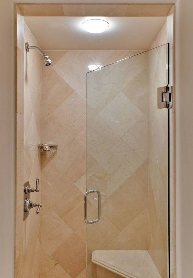 bathroom scene plumbing fixture white shower door bathroom cabinet tan
