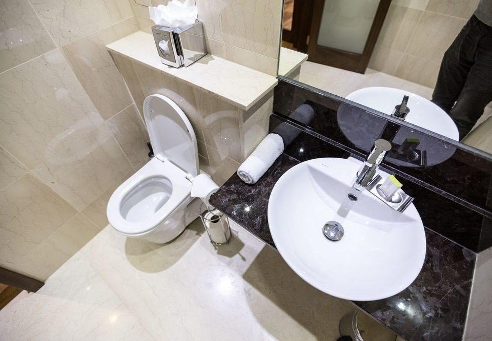 bathroom sink plumbing fixture toilet bidet ceramic flooring bathtub tap tiled