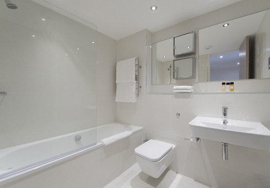 bathroom toilet property sink mirror white vessel bathtub home plumbing fixture bidet residential clean tile tan
