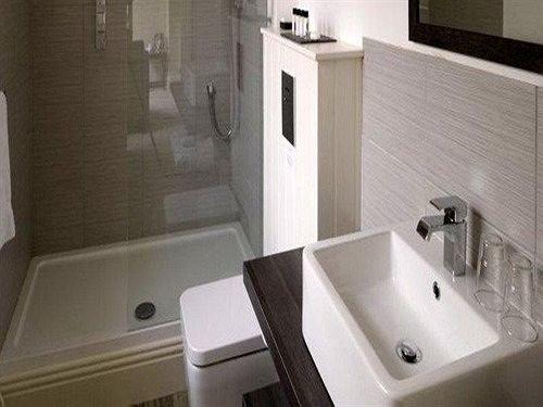 bathroom toilet property sink bidet plumbing fixture white bathtub flooring countertop water basin tiled