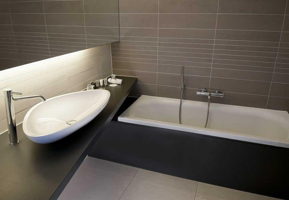 bathroom bathtub plumbing fixture bidet sink flooring tile toilet tiled