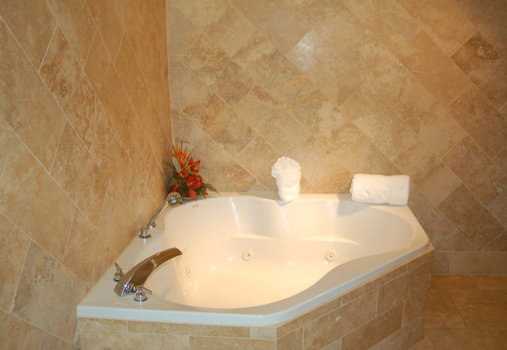 bathroom vessel bathtub swimming pool plumbing fixture flooring bidet jacuzzi white tile tan tiled