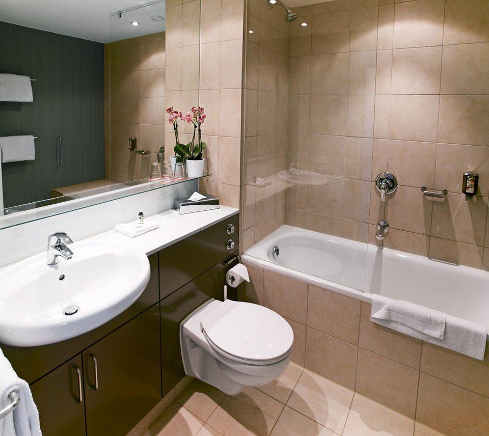 bathroom sink mirror property toilet bidet plumbing fixture bathtub flooring tile tiled