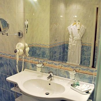 bathroom sink toilet mirror plumbing fixture bathtub bidet swimming pool tile water basin tan tiled
