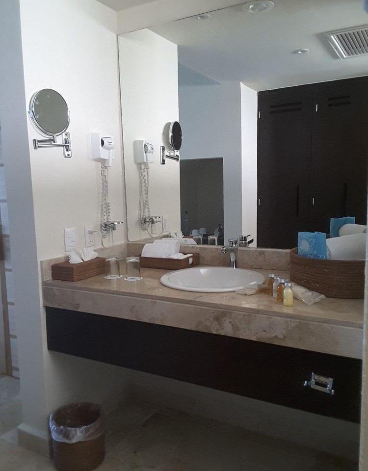 bathroom mirror sink property countertop plumbing fixture bathtub cabinetry toilet