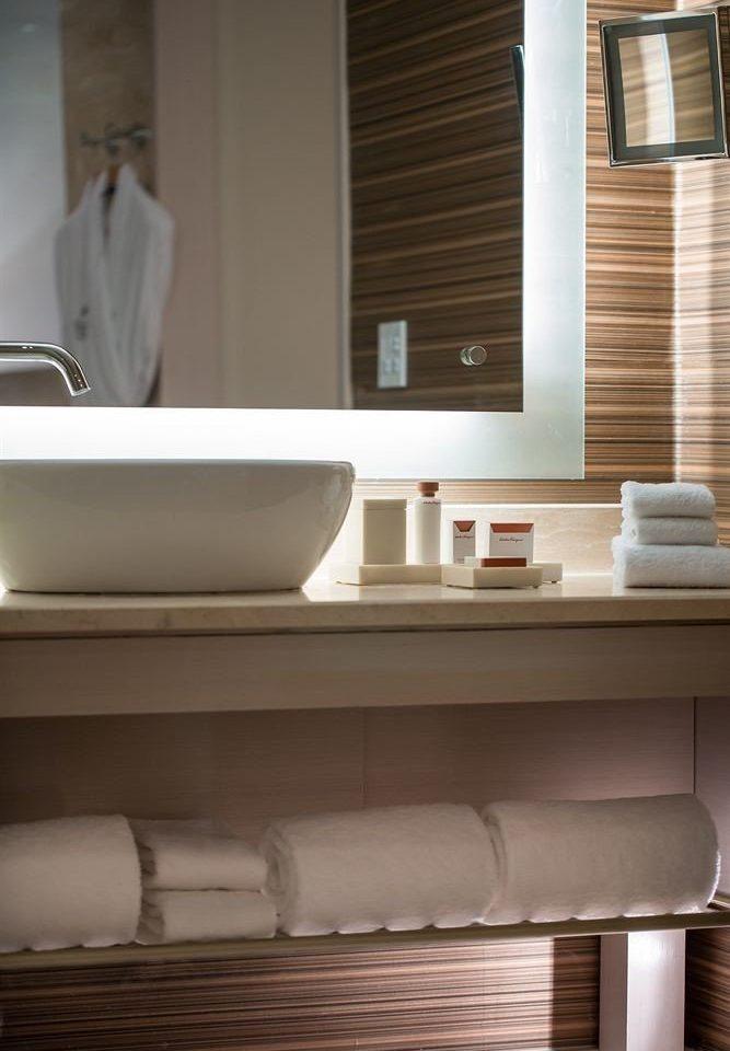 bathroom mirror sink cabinetry plumbing fixture flooring tub bathtub