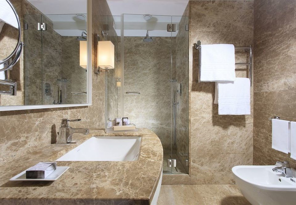 bathroom sink property mirror home toilet plumbing fixture flooring tile tub stone bathtub tiled