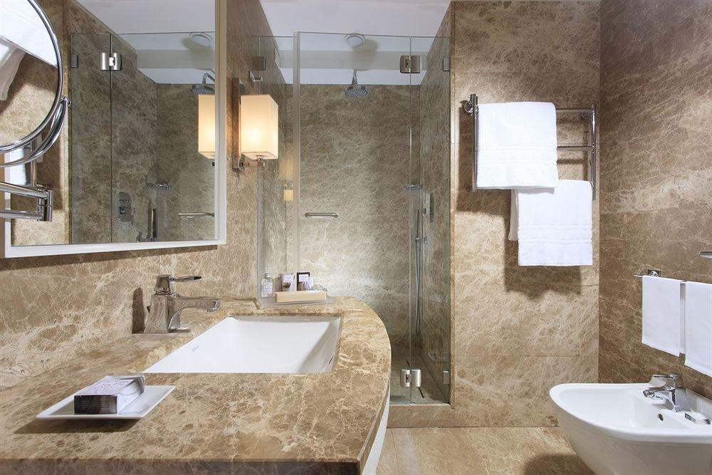 bathroom sink property mirror home toilet plumbing fixture flooring tile tub stone bathtub tiled